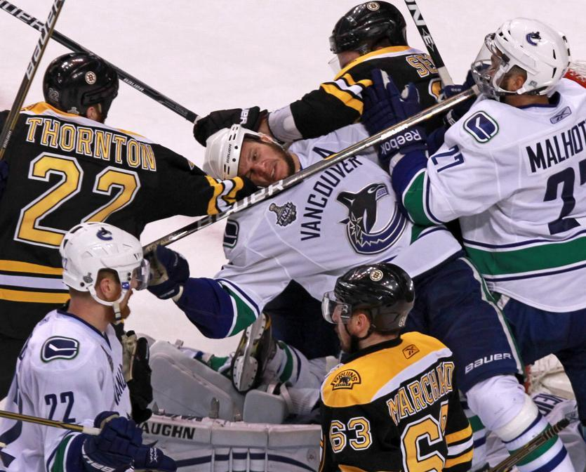 Canucks defenseman Kevin Bieksa, center, got the worst of this pile-up when Vancouver last visited Boston for the Stanley Cup Finals.